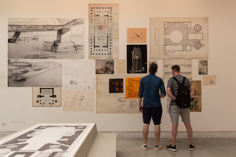 Two men looking at architectural Drawings on a wall curated by Elizabeth Hatz Architects at the Venice Biennale 2018