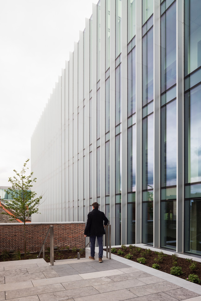 Man walking down steps in the external roof garden with view of office block facade of the Hanging Gardens in Limerick