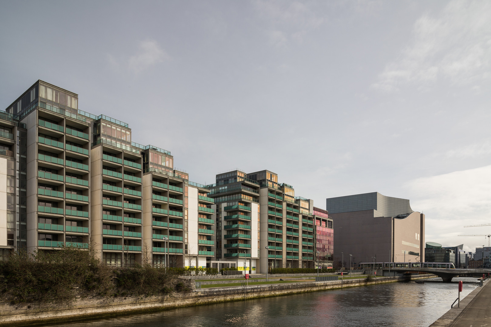 External view of the Spencer Dock Apartments in Dublin from Linear Park with Luas crossing