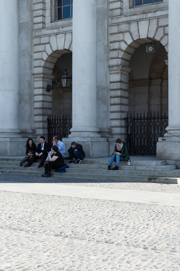 People sitting on steps between classical limestone columns of the portico of a buildng in Trinity College, Dublin