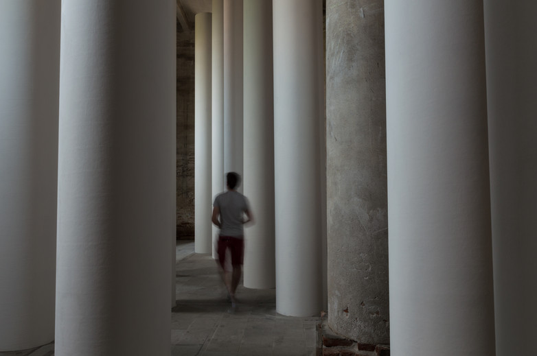 Man walking through white columns of the Valerio Olgiati designed pavilion at the Venice Biennale 2018