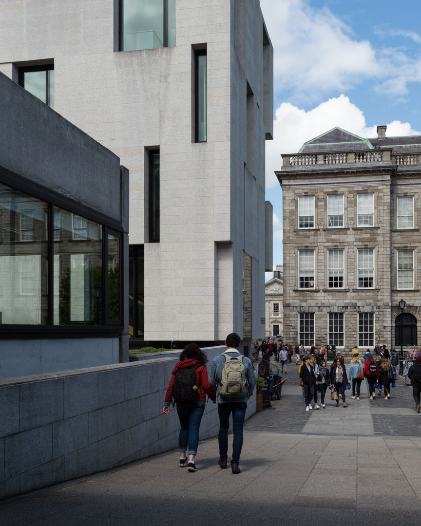 Incised granite slabbed and glazed facade of the Long Room Hub and limestone old library, Trinity College, Dublin