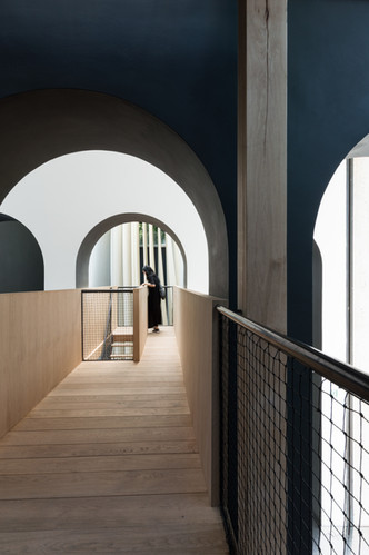 Woman looking down stairs at end of timber bridge under arch at Austria's pavilion at the Venice Biennale 2018