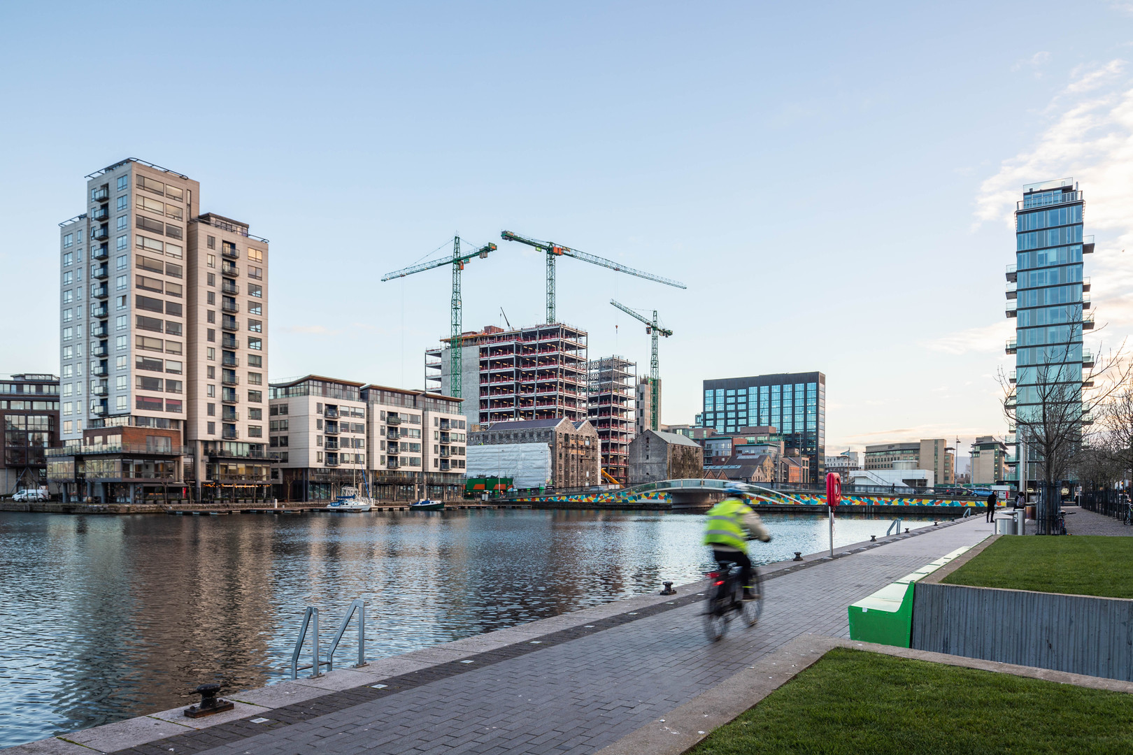 A man cycles along the Grand Canal Dock with Millenium Tower, Boland Mills, Montevetro and Alto vetro in the background