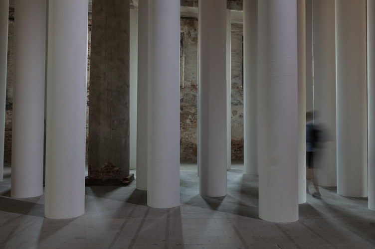 Man walking through white columns of the Valerio Olgiati designed pavilion at the Venice Biennale 2018