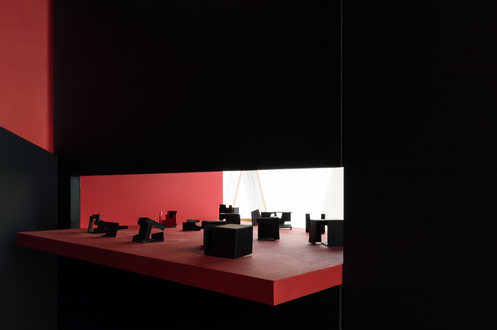 Models inside the black and red pavilion designed by A2 Architects at the Venice Biennale 2018