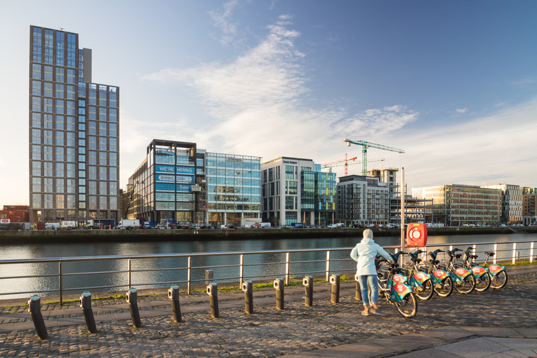 View of Capital Dock from across the Liffey with person parking bicycle in Dublin