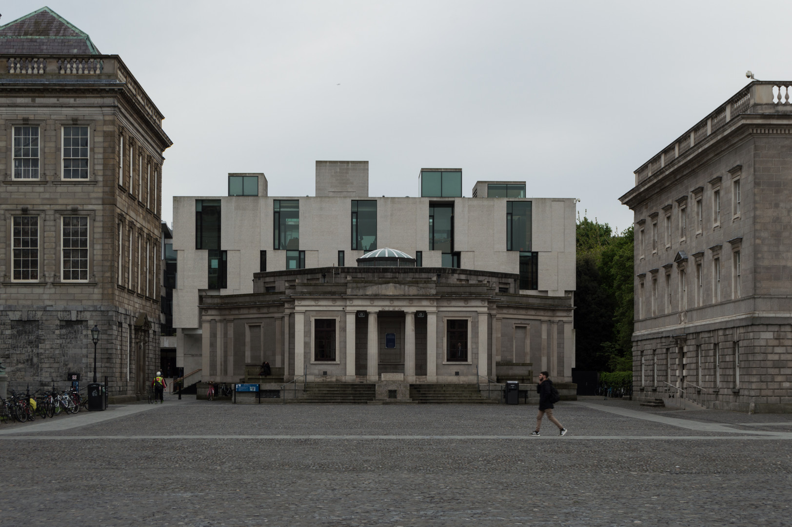 Granite slabbed and glazed facade of the Long Room Hub and surrounded by limestone buildings, Trinity College, Dublin,