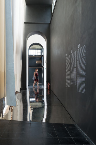 Person passes below arch of black painted room the Austrain pavilion at the Venice Biennale 2018