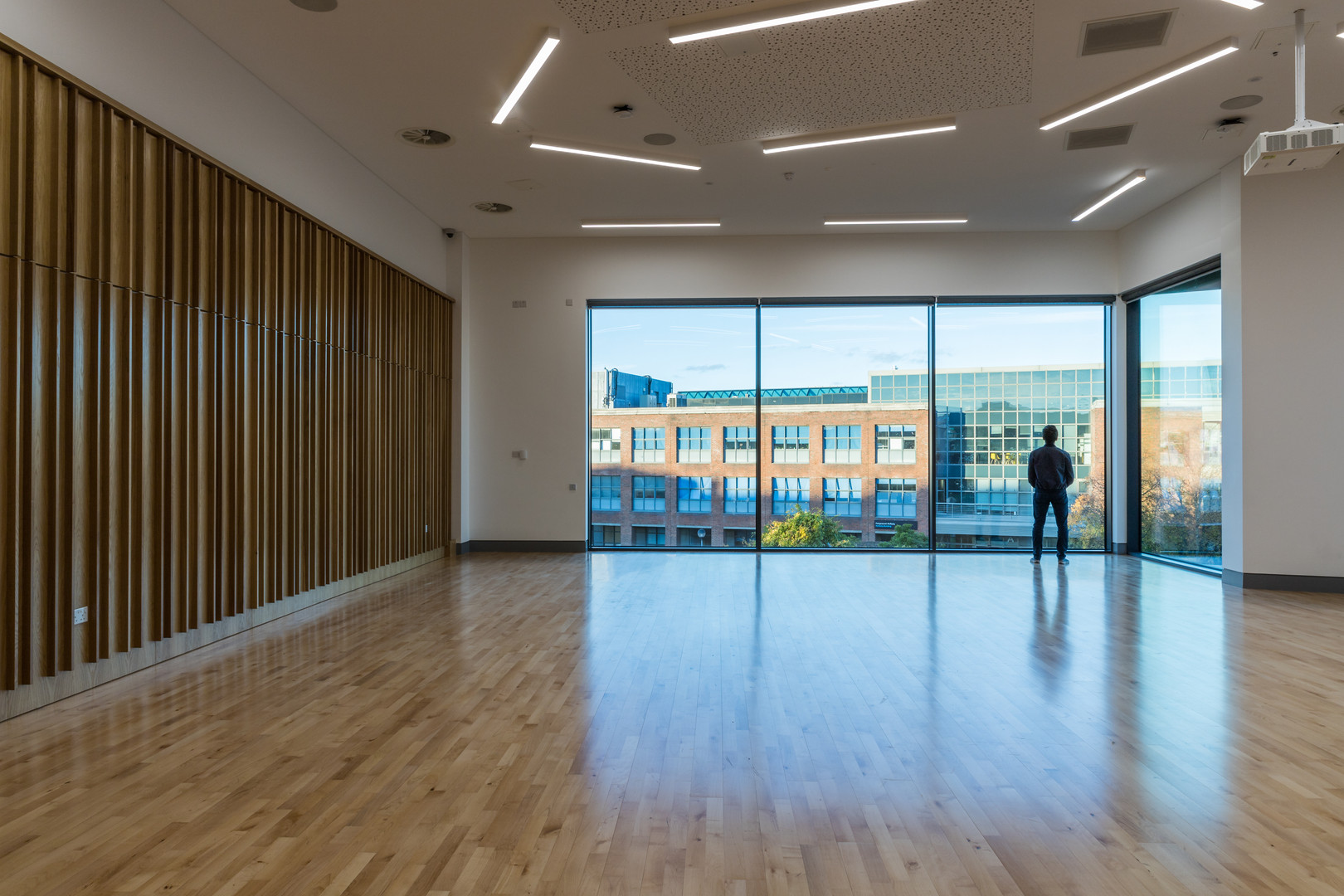 Event room with timber floor, timber soundproof panelling and large window Student Hub in DCU, Dublin