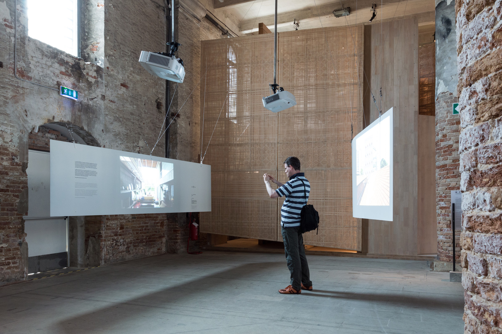 Man in between two hanging screens of Grupo SP pavilion at the Venice Biennale 2018