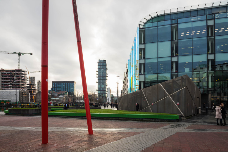 Montevetreo framed between 2 red rods from the Grand Canal Square