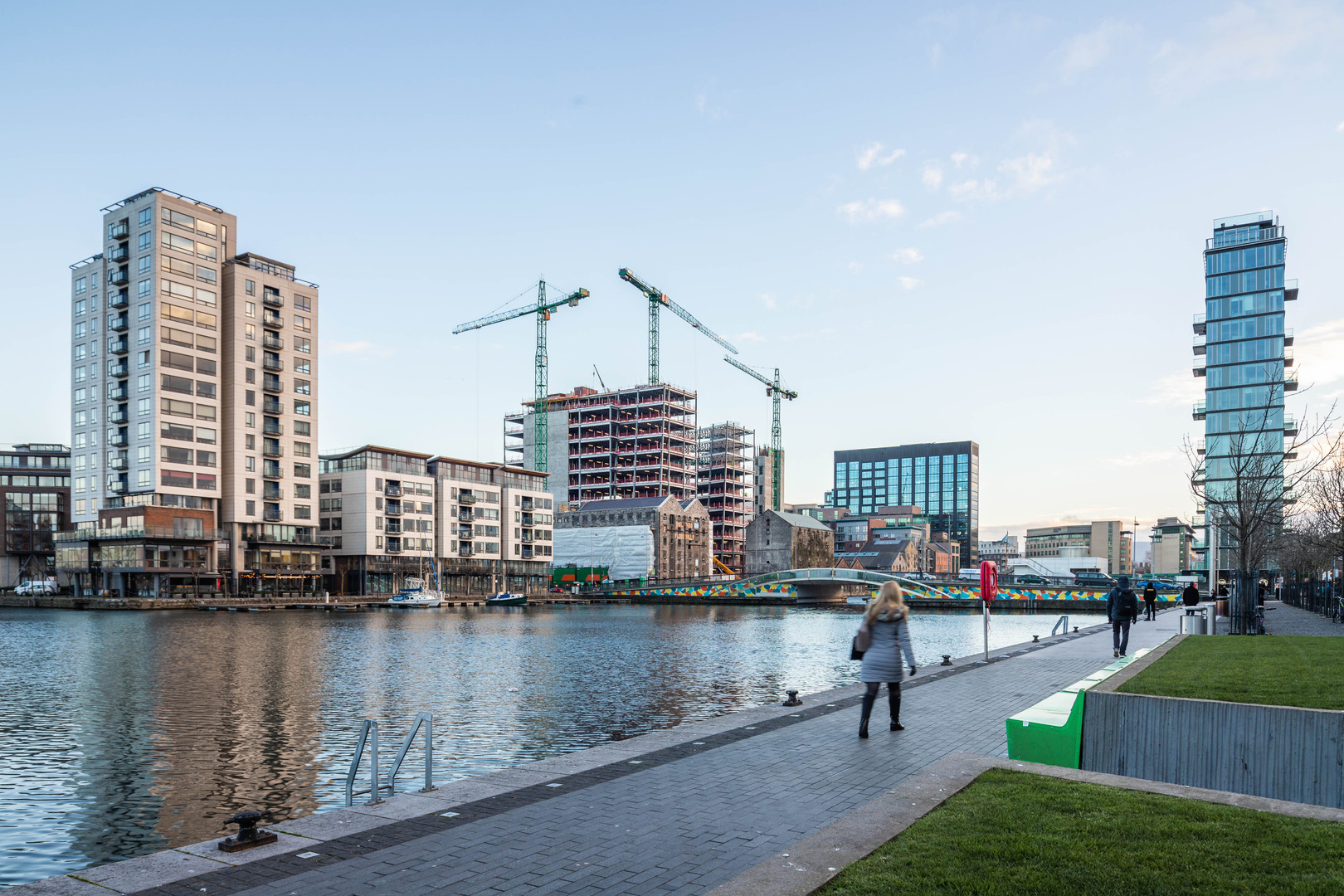 People walk along the Grand Canal Dock with Millenium Tower, Boland Mills, Montevetro and Alto vetro in the background