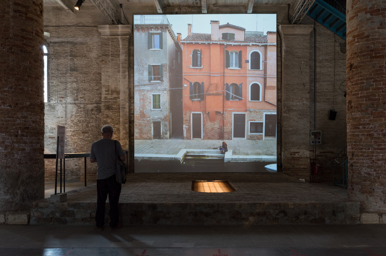 A man standing looking at a screen of the pavilion by Rozana Montiel Estudio de Arquitectura at the Venice Biennale 2018
