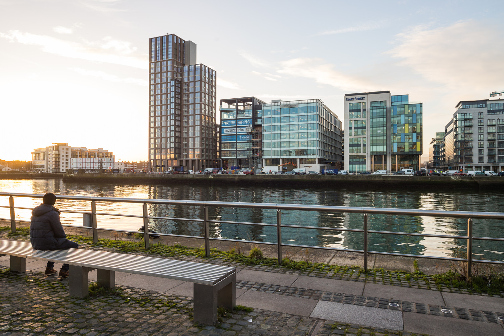 View of Capital Dock from across the Liffey with person sitting on bench in Dublin