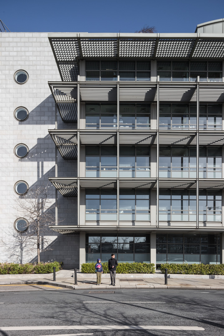 External view of granite clad and glazed facade with circular windows of A&L Goodbody Headquarters in Dublin from North Wall Quay