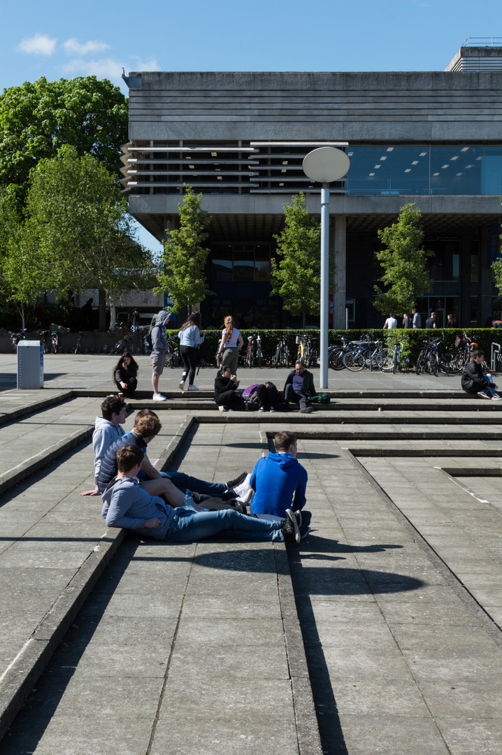 Students sitting on steps in front of the Undercroft of the Library at UCD, Dublin