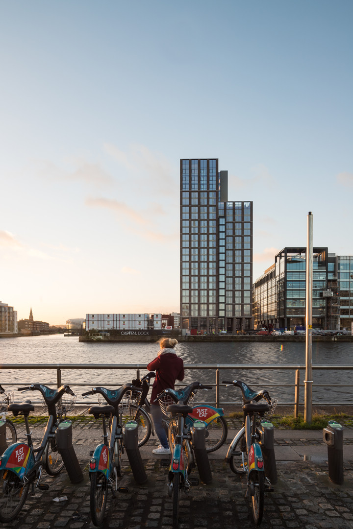 View of Capital Dock from across the Liffey in Dublin with person parking bicycle in foreground