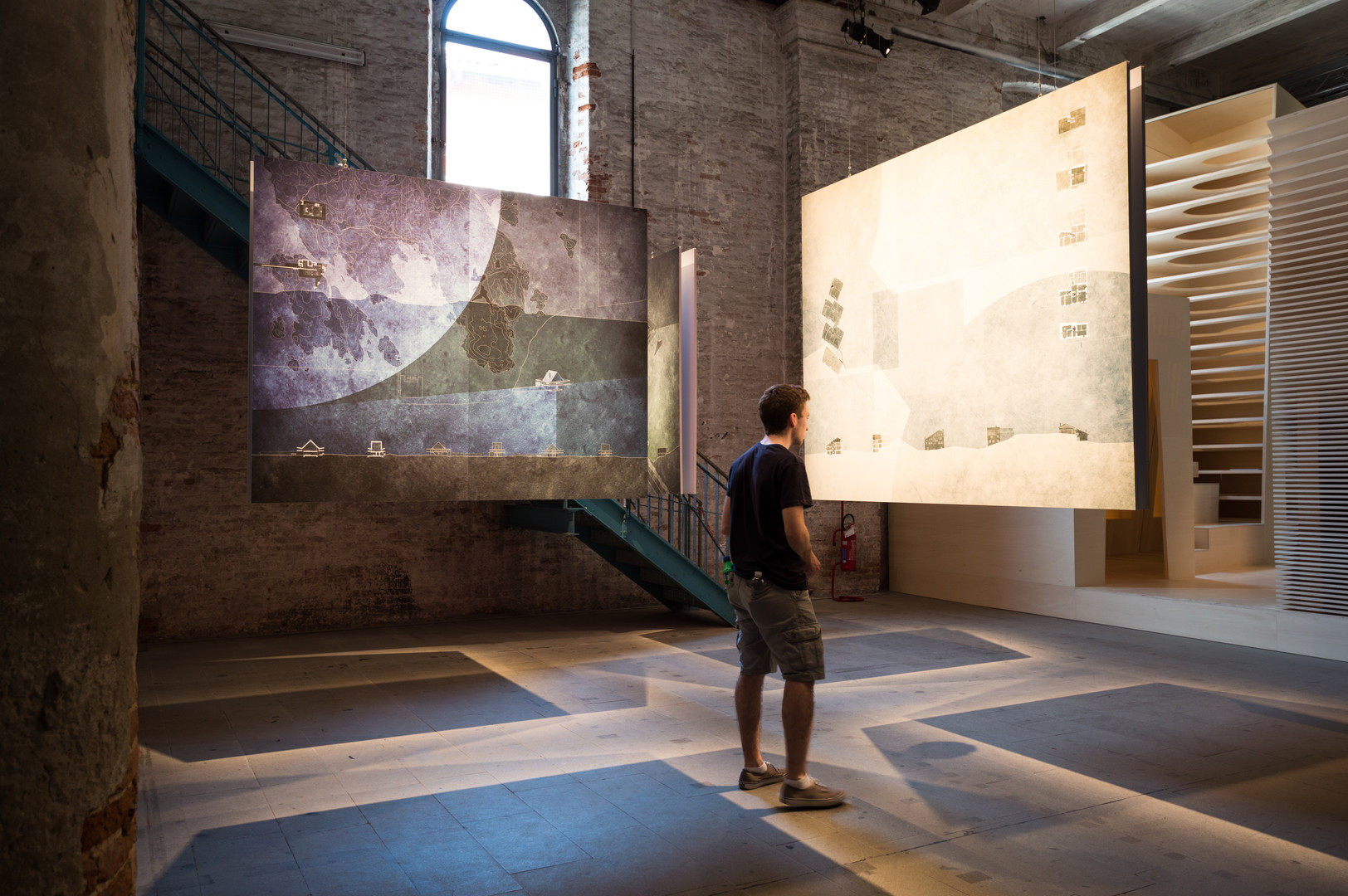 Man looking at hanging drawing of Angela Deuber Architect's pavilion at the Venice Biennale 2018