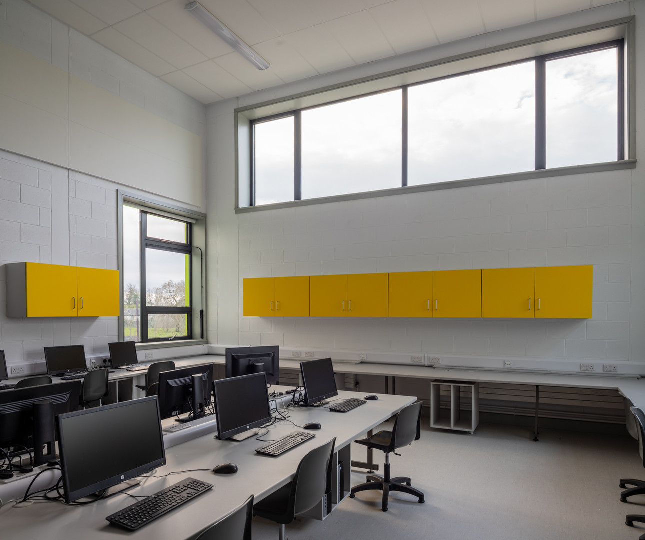 Computer room with desks, computers, white block walls and yellow cupboards in Colaiste Iosaef, Kilmallock, Limerick