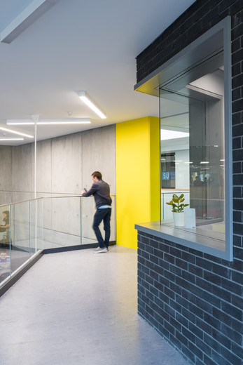 Man standing at balustrade of the mezzanine of the Student Hub in DCU, Dublin