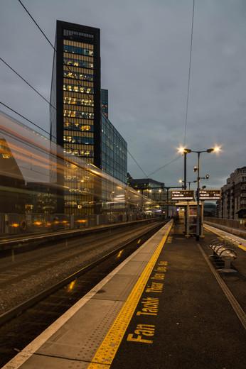 Train passing along track in front of Montevetro in Dublin at dusk