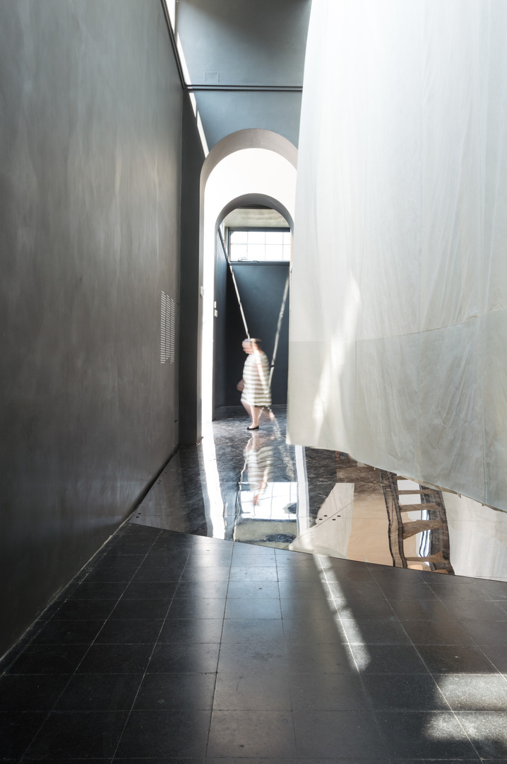 White curtain blowing over black tiled floor as man walks by in the Austrain pavilion at the Venice Biennale 2018