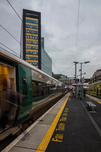 Person entering train along track in front of Montevetro in Dublin at dusk