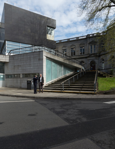 Two men standing at bottom of step leading to the entrance of the Department of Mechanical & Manufacturing Engineering