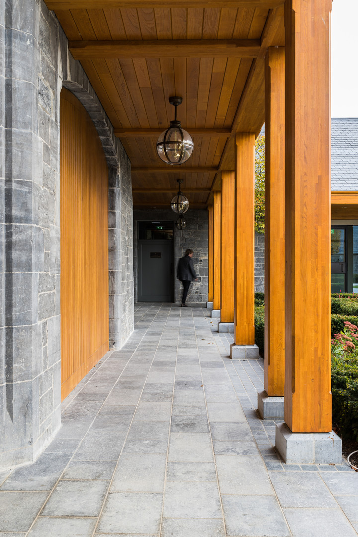 Man walking through timber arcade of Adare Manor Clubhouse, Limerick
