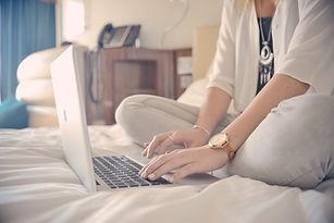ベッド上のノートパソコンのタイピング