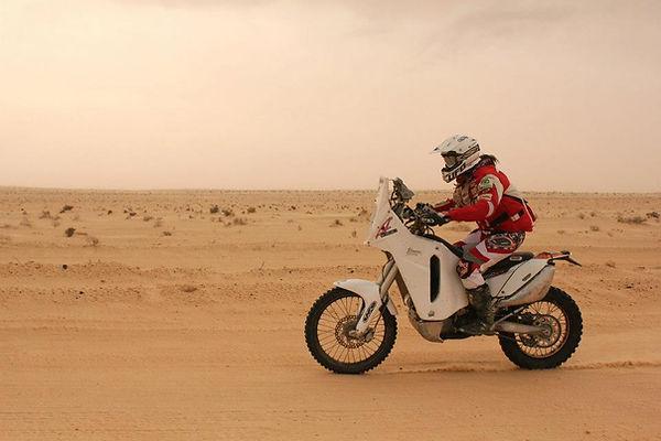 Deserto africancon donna in moto e paracollo smotard