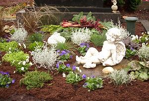 Schön gestaltetes Grab mit weißem Puttenengel