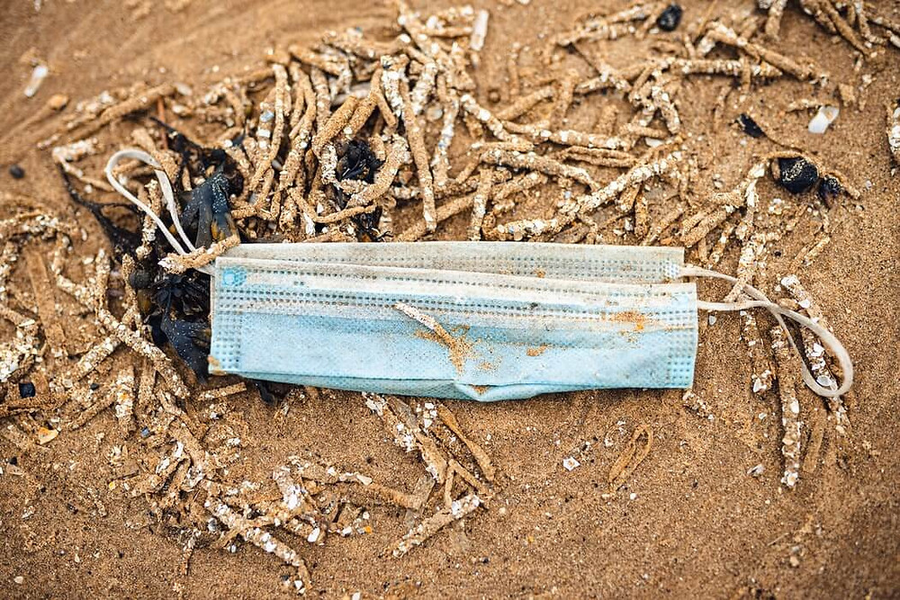 A blue, used, disposable mask found on a beach covered in sand and surrounded by debris