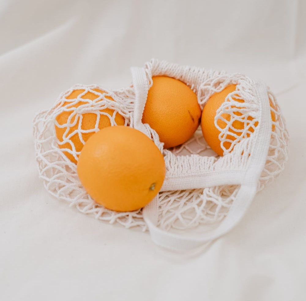 A knitted, reusable produce bag filled with oranges