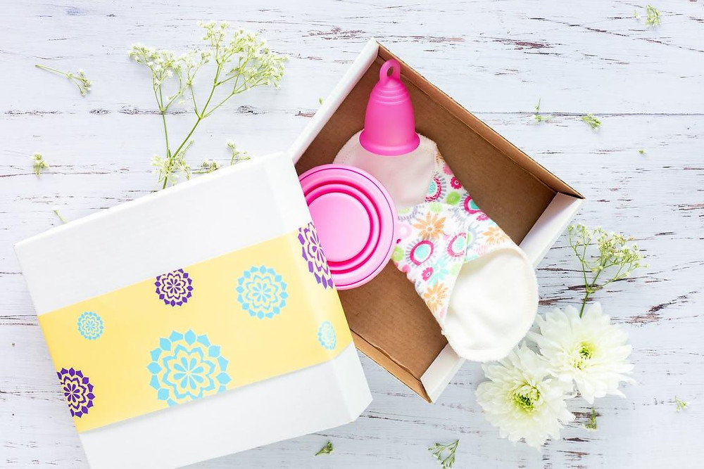 An eco-friendly menstrual kit with a pink menstrual cup, a white reusable pad and a pink container inside a white box