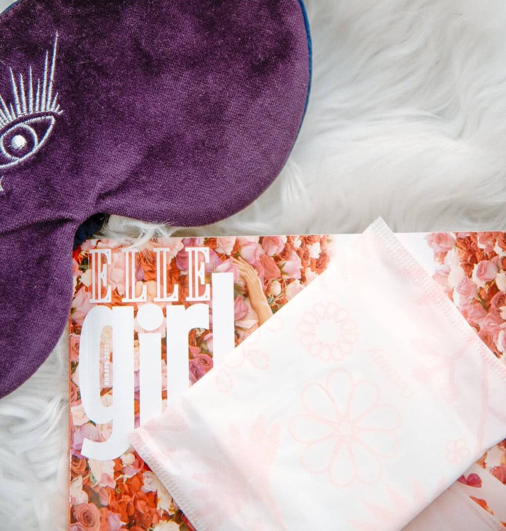 Pembalut yang belum dibuka dan masih tertutup dengan pembungkus plastiknya diatas majalah Elle girl dan terdapat masker tidur