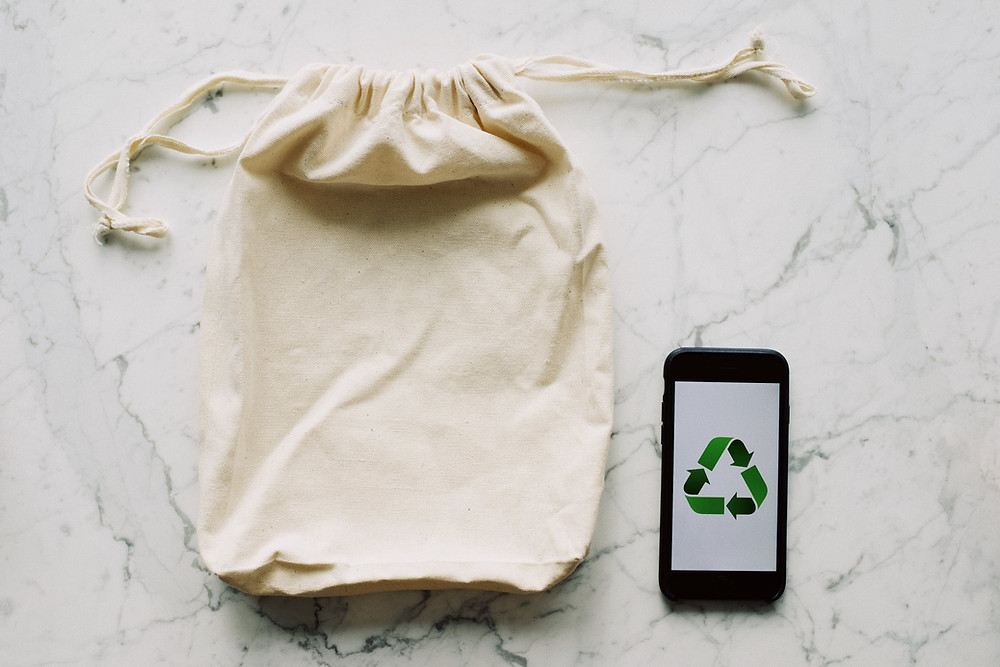 A plain cloth pouch and a phone with a recycle sign on a marble top