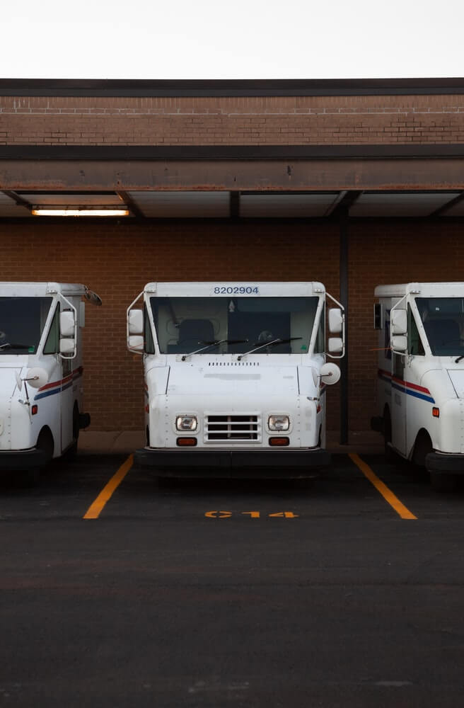 Three parked white delivery trucks lined up waiting to deliver packages