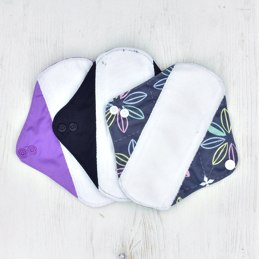 Three reusable pads with different patters on a white wooden background
