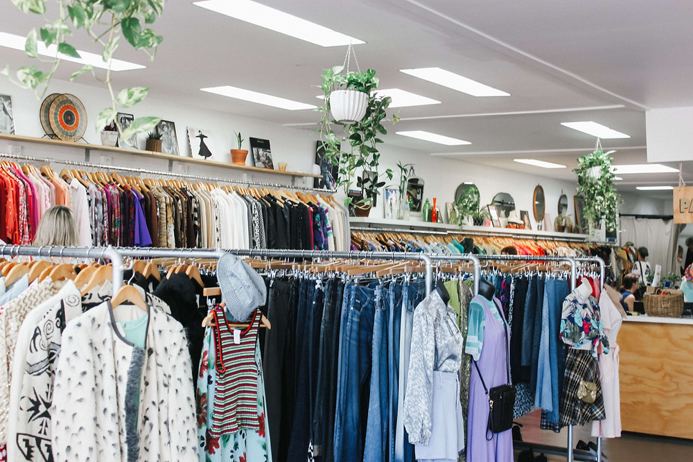 A well lit thrift shop with a wide range of clothes and knick knacks