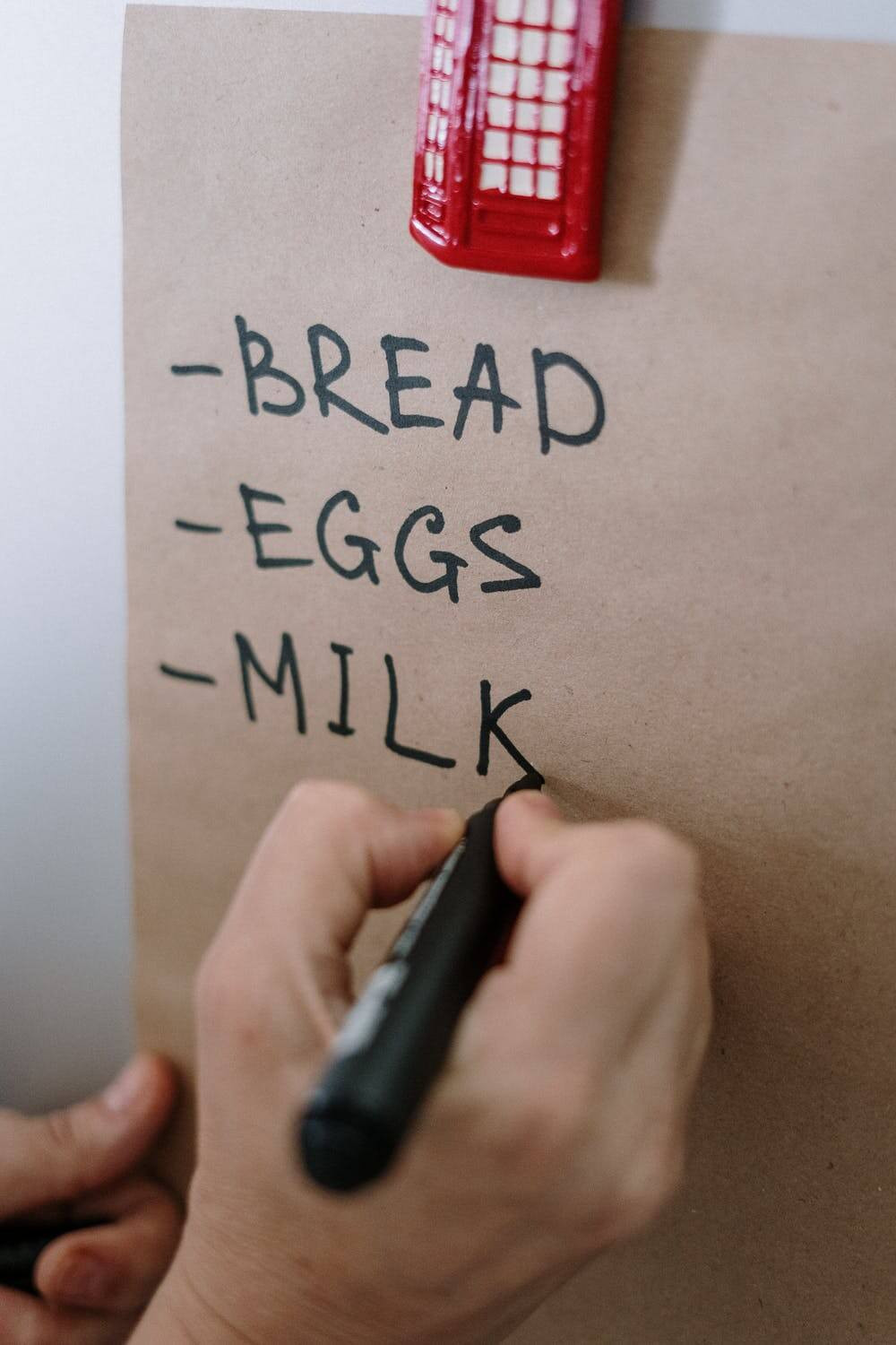 A person writing a shopping list which consists of bread, eggs and milk