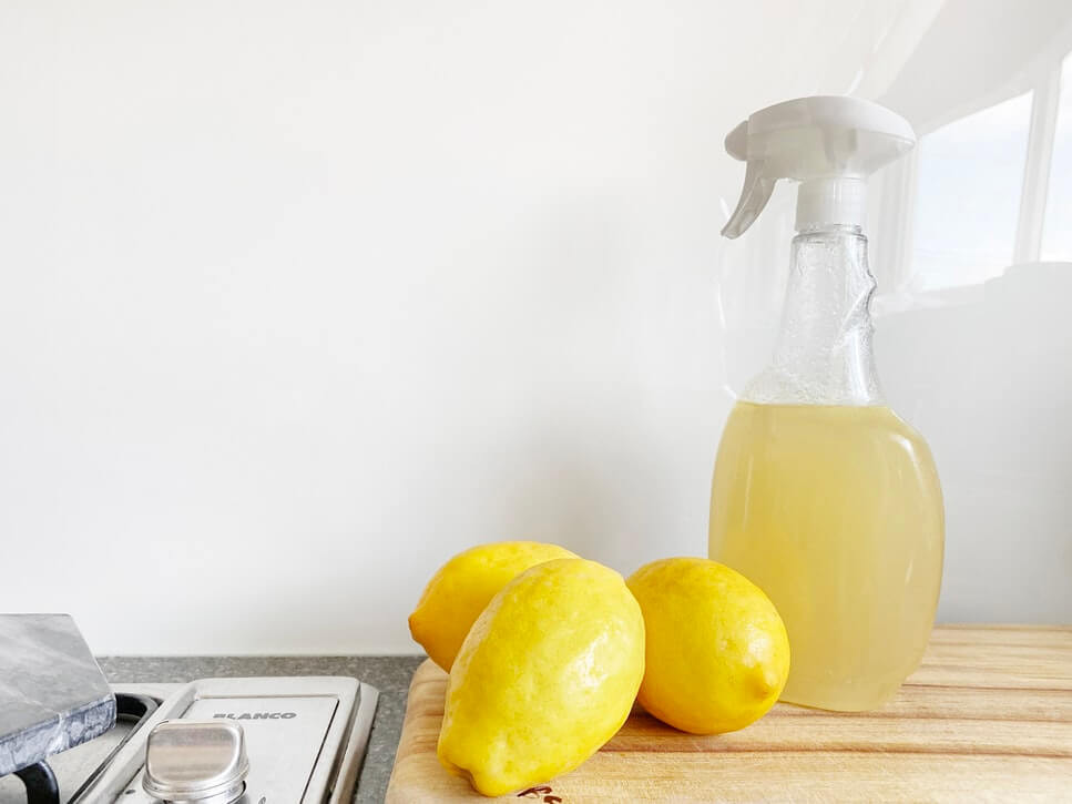 A citrus cleaning spray in a spray bottle with three lemons beside it