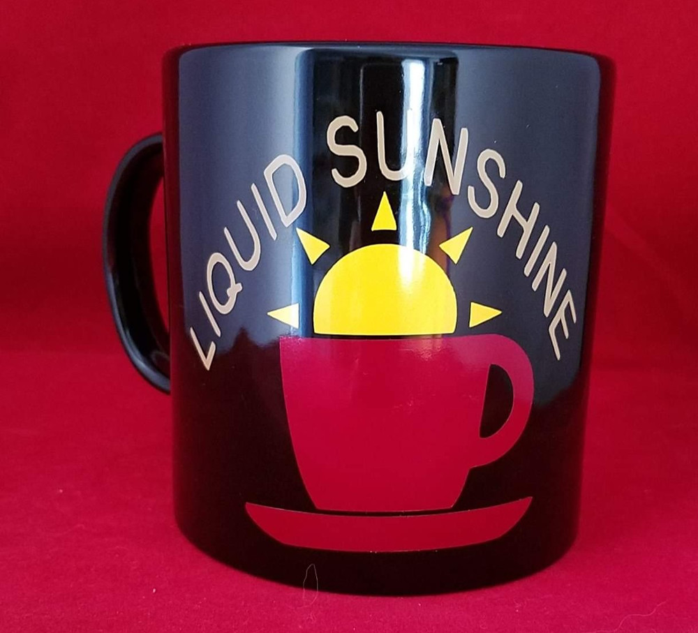 Liquid Sunshine is declared above a black mug featuring the sun rising from a red coffee cup.