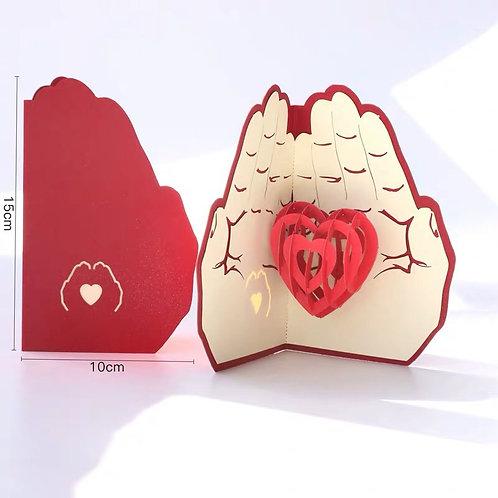 Hands holding heart pop up card