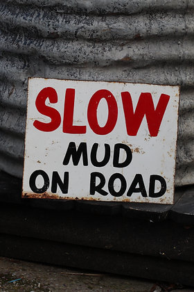 Slow mud on road sign
