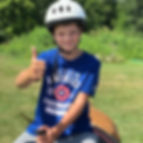 Boy giving the thumbs up while on a horse at camp