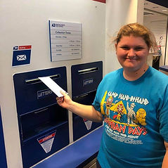 Participant mailing a letter at the post office