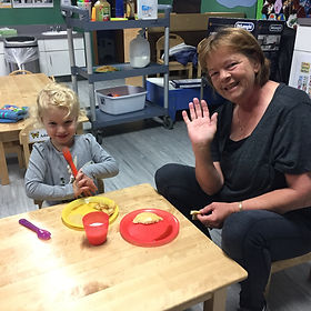 young child and volunteer in childcare room