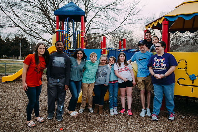 Nine people and participants standing in front of the playground